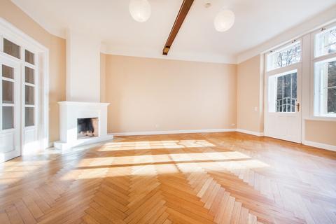 Wohnzimmer mit offenem Kamin Herrschaftliche 5-Zimmer-Altbauwohnung mit Kamin und Südbalkon