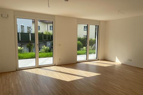 Wohnzimmer mit offener Küche und hellen Fensterfronten Eleganter Minimalismus!<br /> <br /> 4-Zimmer-Gartenwohnung <br /> in modernem Architektur-Ensemble